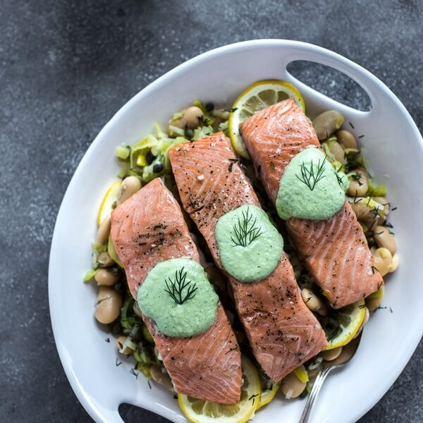 Three pieces of Slow-Baked Salmon with Butter Beans in a plate over greens
