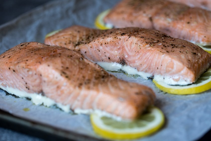 Close up view of three Slow-Baked Salmon from the oven placed on lemon slices