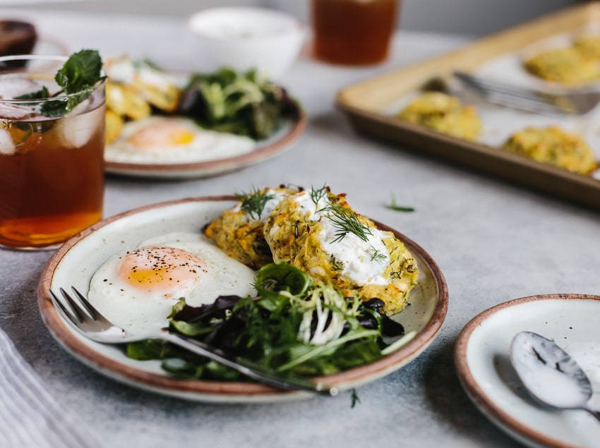 a plate of baked courgette fritters recipe topped off with yogurt and served with eggs