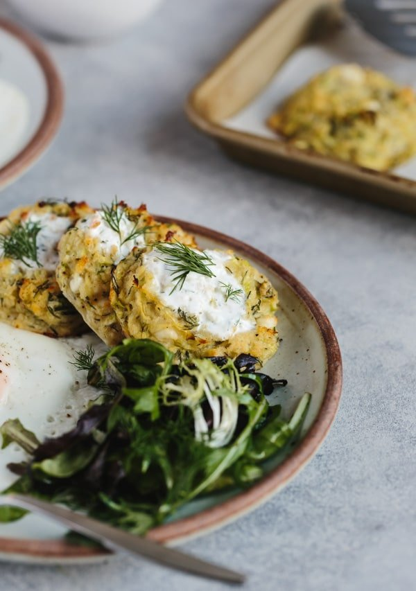 Baked courgette fritters topped off with yogurt sauce and served with a green salad.