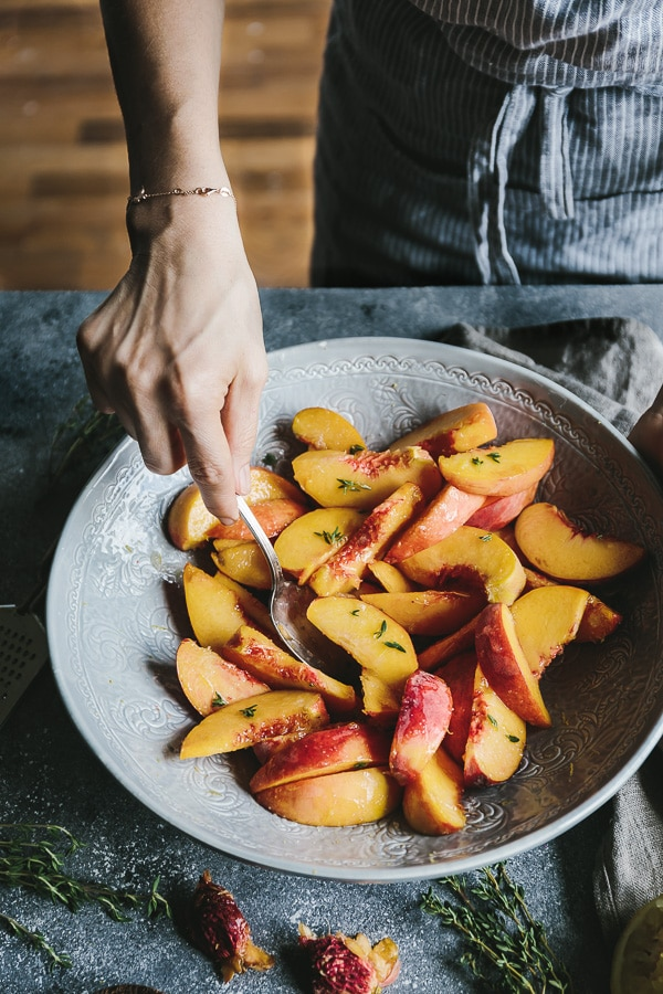 a woman is mixing a bowl of peaches