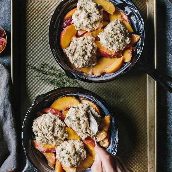 a woman is serving Peach Cobbler with Cornmeal Thyme Biscuits from the top