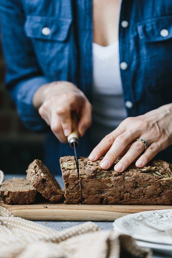 A woman is slicing a Vegan Zucchini Bread from the front view