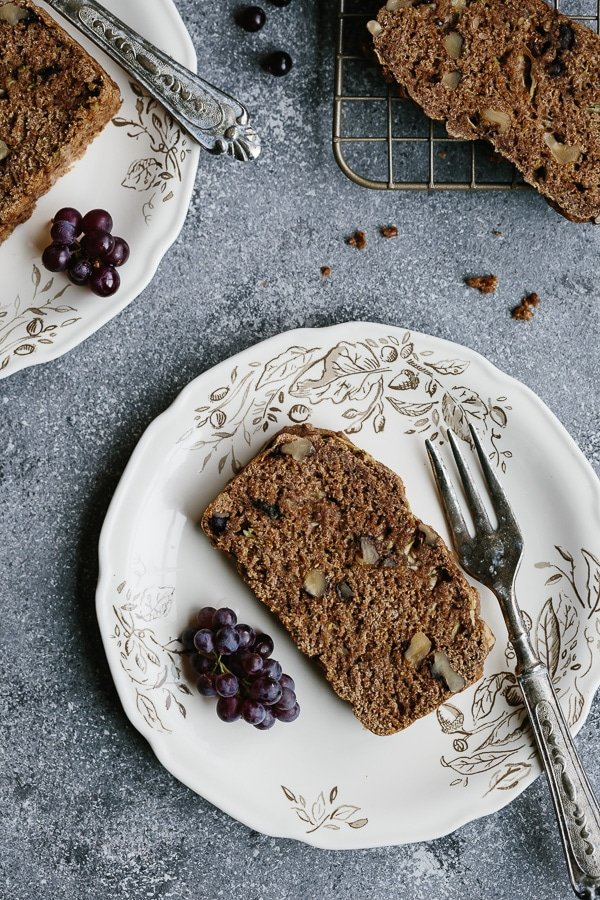 A slice of Vegan Zucchini Bread on a plate for breakfast with coffee.