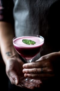 Person holding a glass of Blueberry, Dark Cherry and Calvados Cocktail