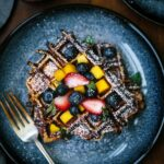 A plate with layered brioche waffles topped off with fruit and sprinkled with powdered sugar from the top view.