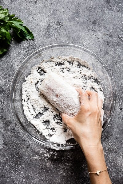 Person showing How to season fish by dreading it in flour