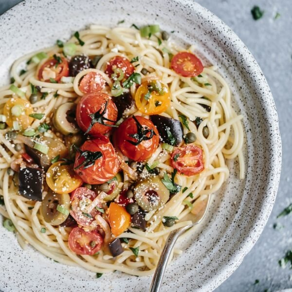 A bowl of Eggplant Pomodoro Pasta topped off with tomatoes in a bowl.