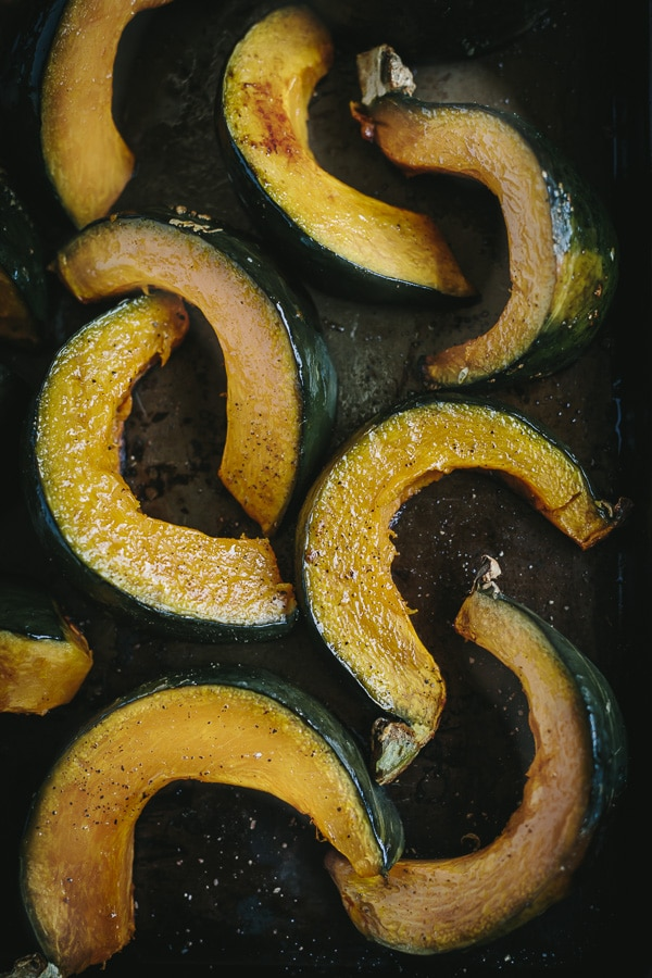 Slices of roasted Kabocha Squash on a baking sheet