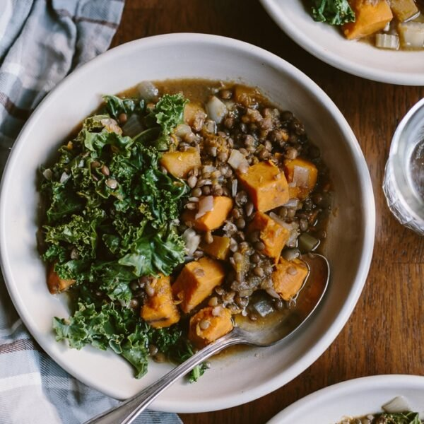 A bowl of Slow Cooker Butternut Squash Lentil Stew Recipe with a spoon on the side