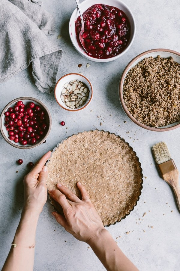 A woman is prepping the tart dough for vegan cranberry pie from the top