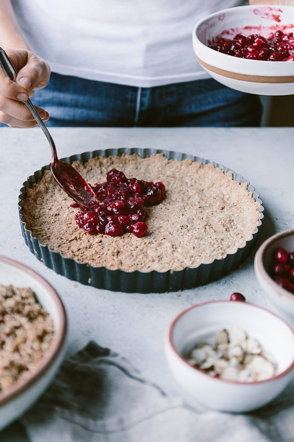 Person placing the cranberry sauce onto walnut crust