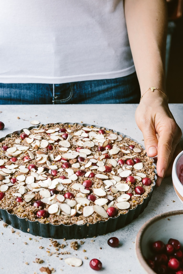 Woman serving vegan almond tart with sliced almonds on top