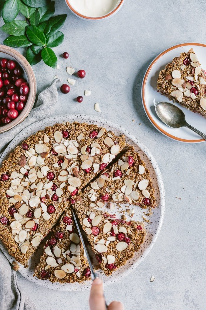 Cranberry Almond Tart as a person is slicing it from the top view