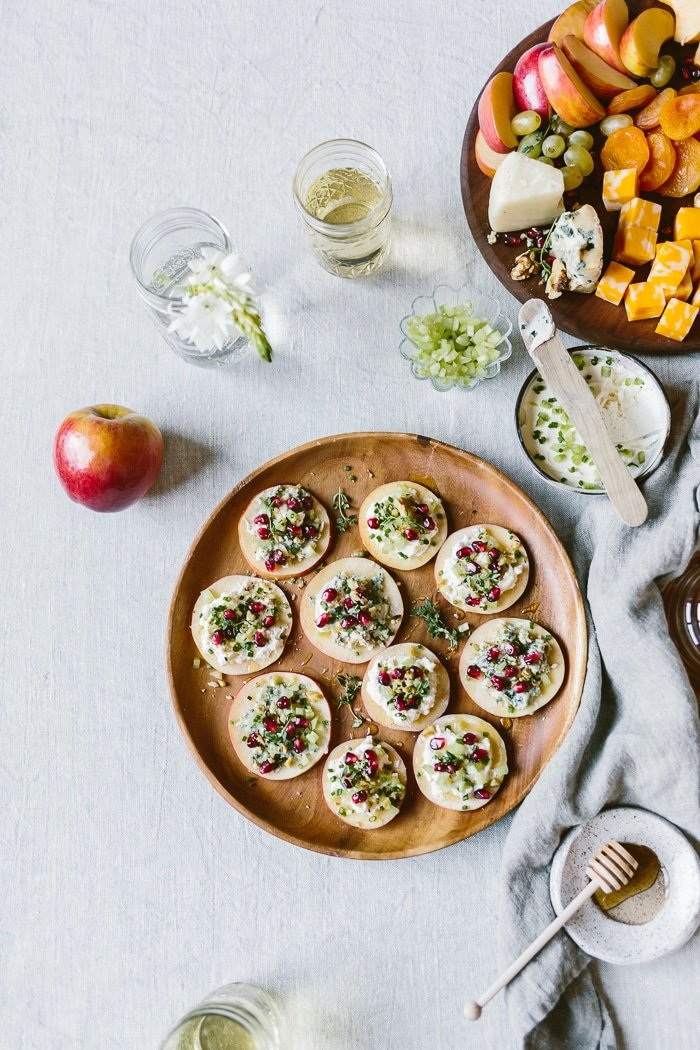 "Cheesy Apple Bites with Walnuts, Celery, and Pomegranate Seeds: The easiest appetizer made with apple ""crackers"" topped off with cream cheese, walnuts, celery, and drizzled with honey."