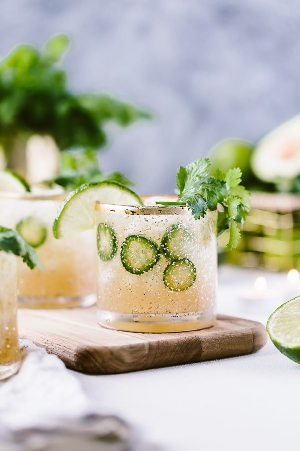 Jalapeno Margaritas placed on a wooden cutting board and garnished with lime