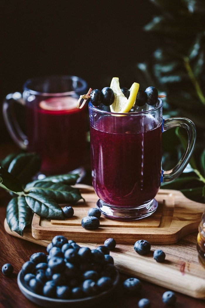 Close up view of a glass of Honey Sweetened Blueberry Hot Toddy garnished with a slice of lemon and blueberries and another hot toddy