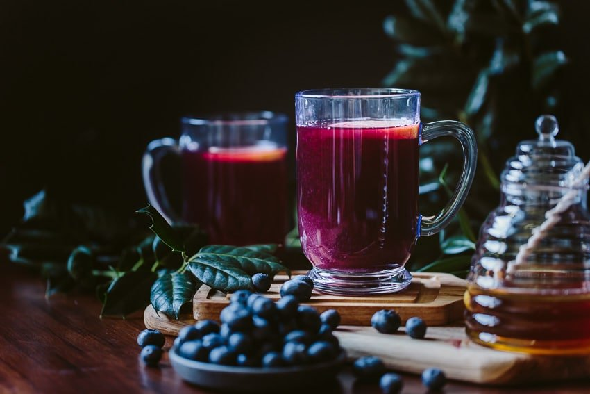 Two glasses of blueberry hot toddy surrounded by a bowl of blueberries and a jar of honey