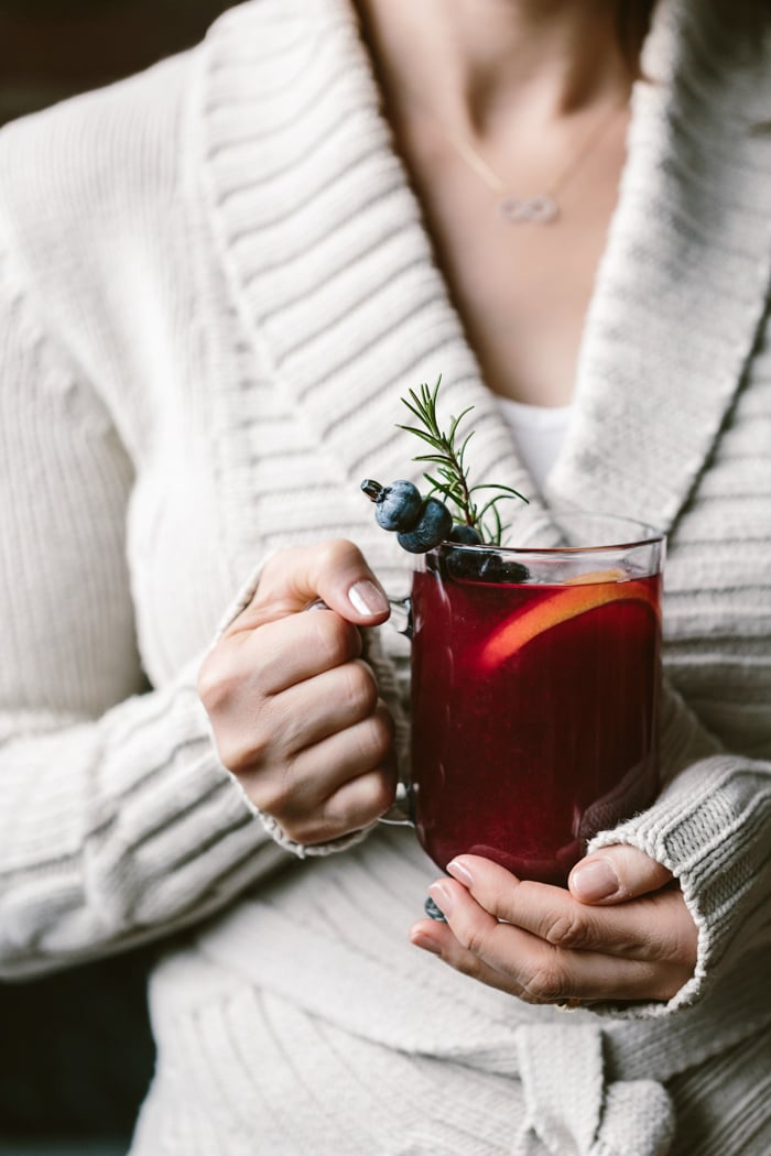 A woman holding a glass of honey sweetened blueberry hot toddy
