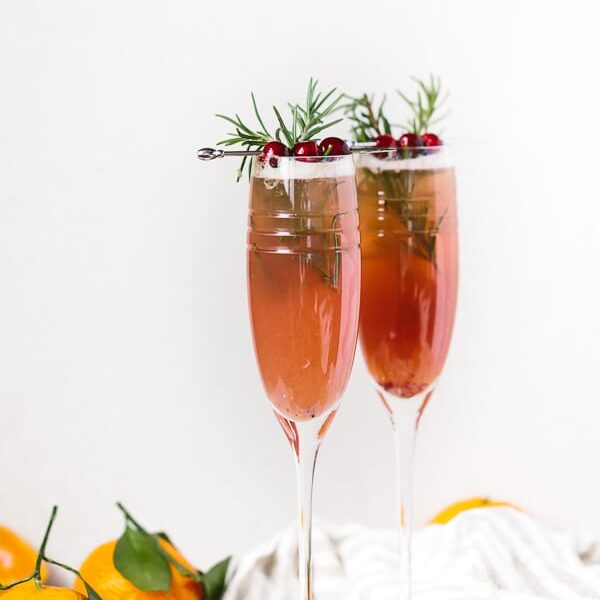 2 flutes of Clementine Cranberry Prosecco Cocktail: An easy to make cranberry and clementine flavored prosecco cocktail recipe for all your upcoming holiday parties.