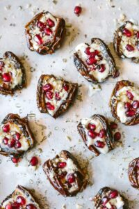 Stuffed dates with mascarpone cheese and pomegranate seeds on a sheet pan.