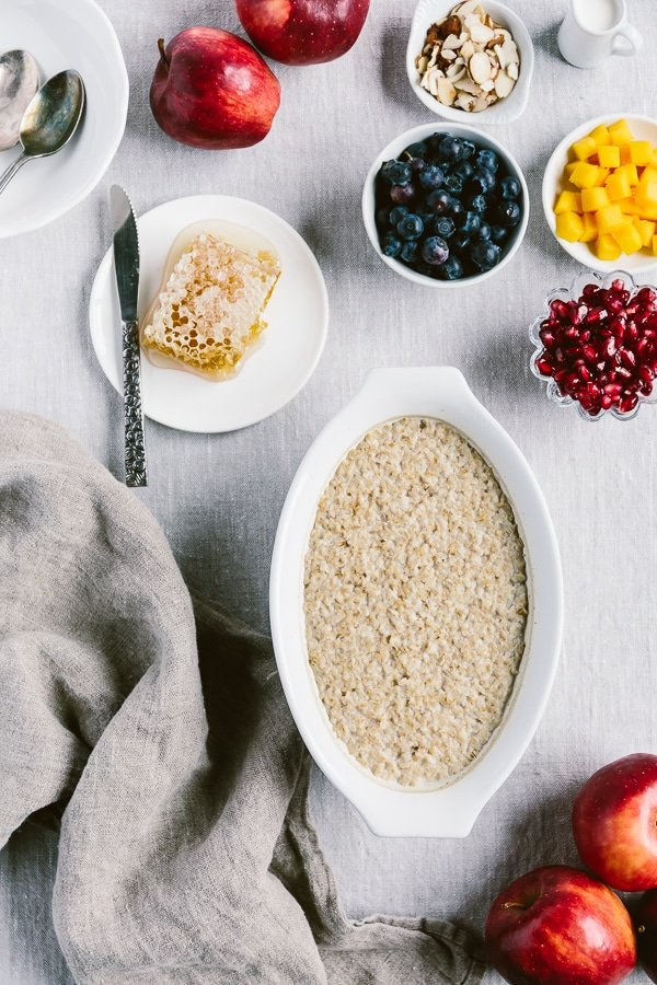 A bowl of Crock Pot Steel Cut Oats photographed from the top with fruits and honey around it.