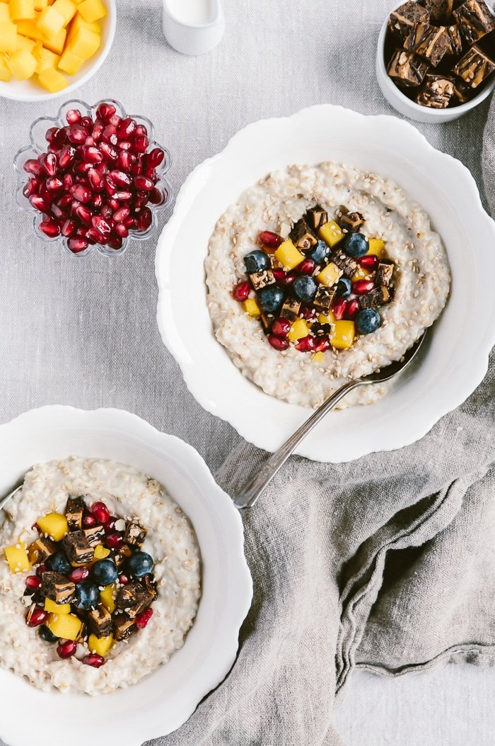 Learn how to make steel cut oats in slow cooker Two bowls of overnight steel cut oats in crockpot topped off with fruit photographed from the top view with more toppings around them.