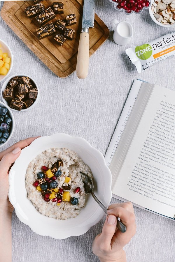 A woman is photographed from the top view as she is eating oatmeal while reading a book.