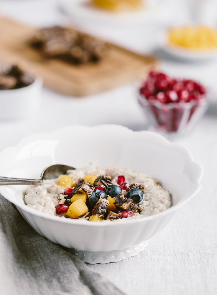 A bowl of cooked oats photographed from the front view close up with fruit on top.