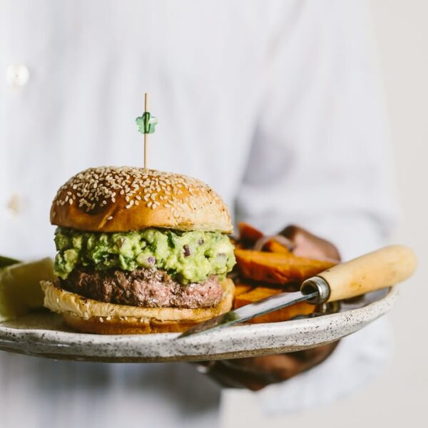 Person holding a Guacamole Burger served with roasted red onion and sweet potato on the side