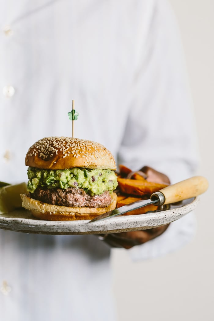 Person holding a Guacamole Burger served with roasted red onion and sweet potato on the side on a plate with a knife
