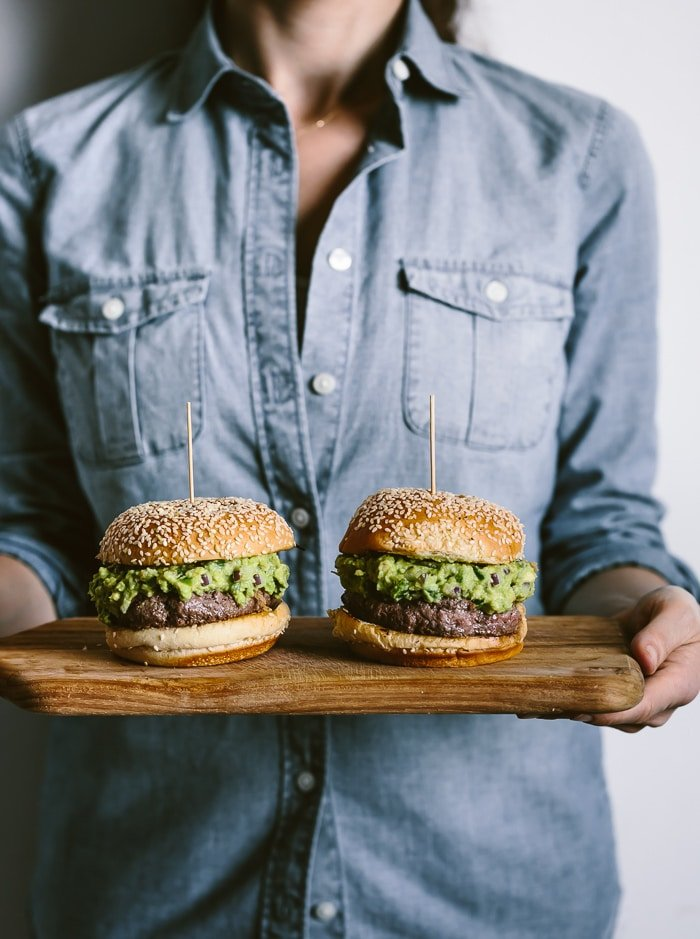 Person 2 Guacamole Burgers served on a wooden platter