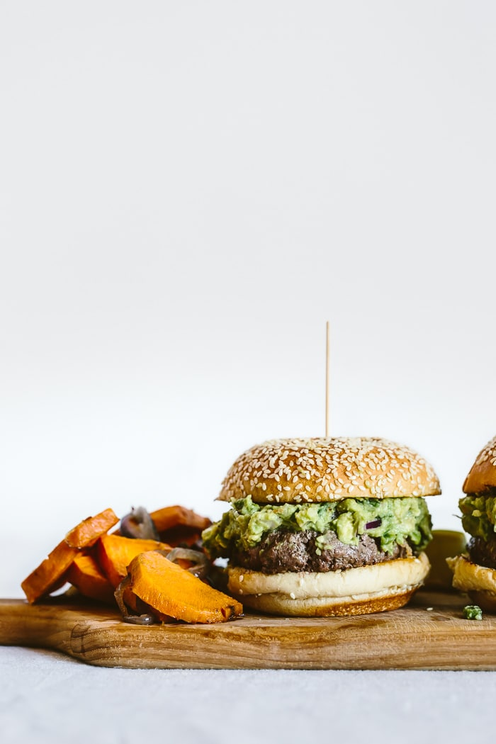 Close up shot of Guacamole Burgers and roasted red onion and sweet potato on the side served on a wooden platter