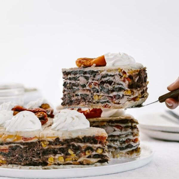 Chicken Quesadilla Cake with a single serving removed and raised: Layers and layers of Mexican flavors stacked up in a 9-inch cake and topped off with sweet peppers and sour cream.