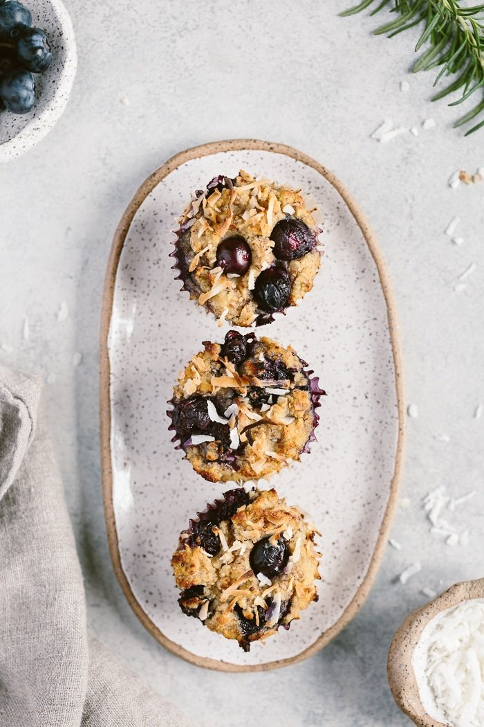 three coconut flour blueberry muffins placed on a plate