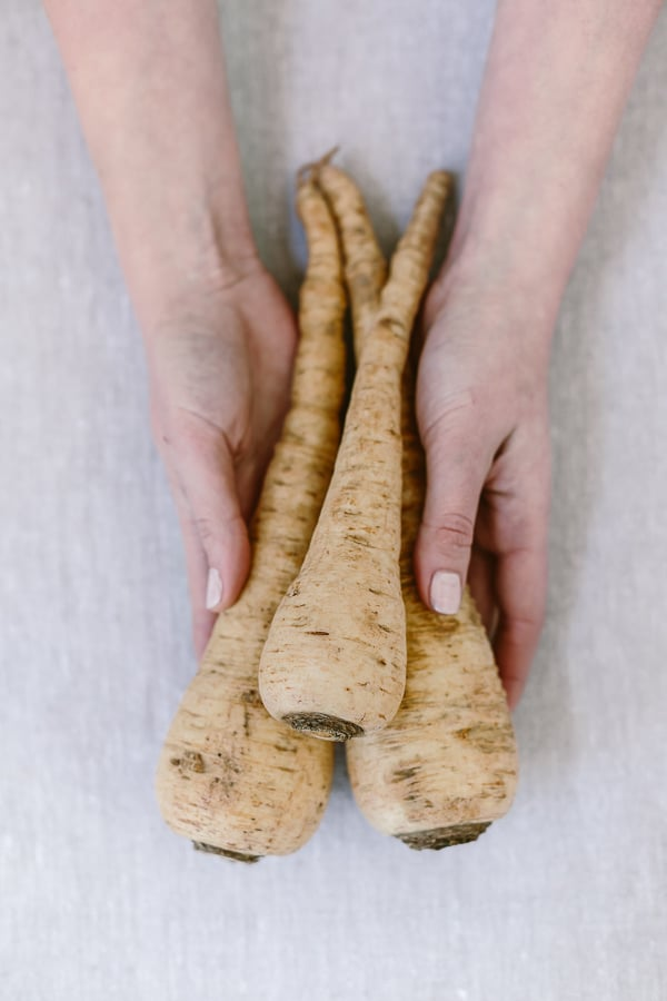 Person holding 3 parsnips