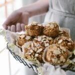 A woman is holding a basket of Parsnip Morning Glory Bran Muffins