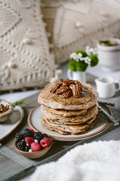 Buckwheat Pancakes Recipe on a bed setting with flours and tea in the background