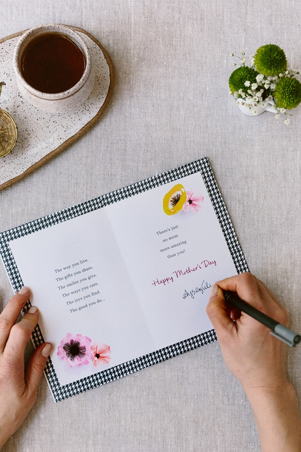 A woman is writing a greeting card