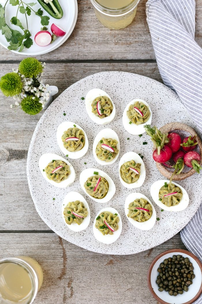 Avocado Deviled Eggs: Hard boiled egg yolks mixed in with avocado, capers, cilantro, and jalapeños to make these delicious deviled eggs.
