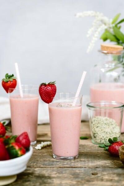A few glasses of strawberry banana yogurt smoothie with straws