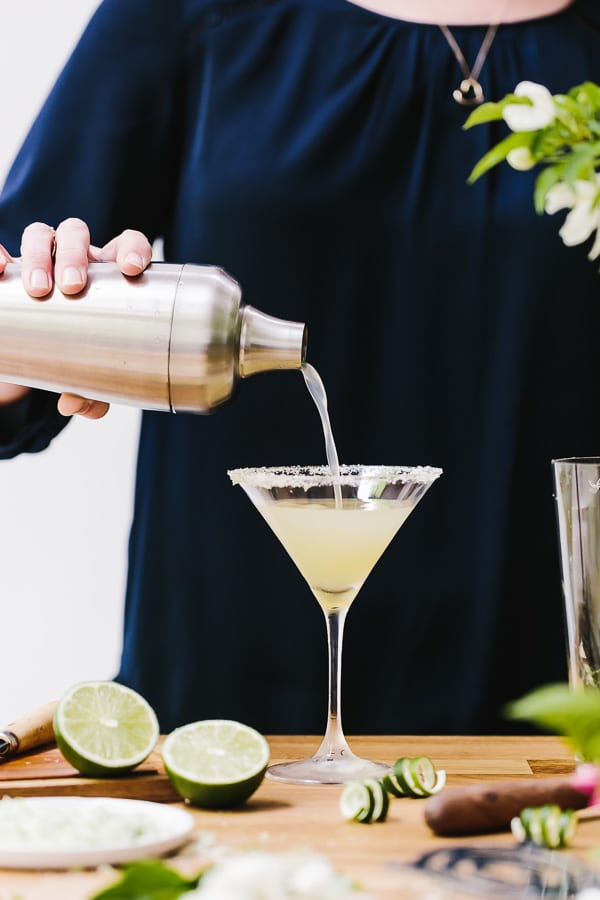A woman is pouring a Recipe of Lime Martini made with mint flavored simple syrup into a glass