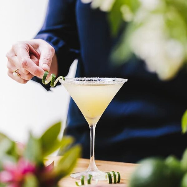 A woman is garnishing a glass of Recipe for Lime Drop Martini made with mint flavored simple syrup with lime