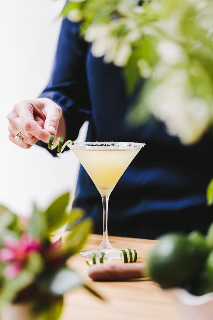 A woman is holding a lime garnish for the Recipe for Lime Drop Martini made with mint flavored simple syrup.