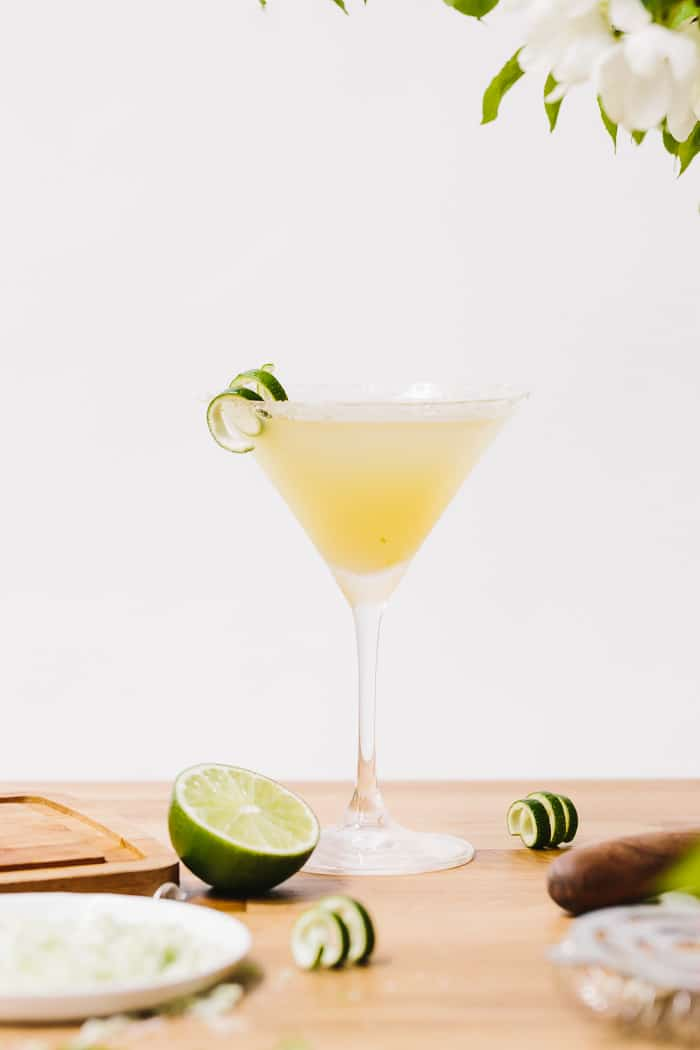 A glass of Lime Drop Martini made with mint flavored simple syrup garnished with lime skin