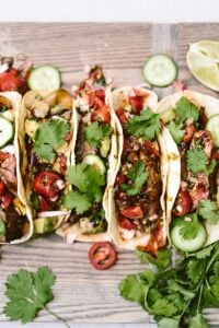 Recipe for Grilled Flank Steak Tacos with a foolproof flank steak marinade placed on a wood cutting board