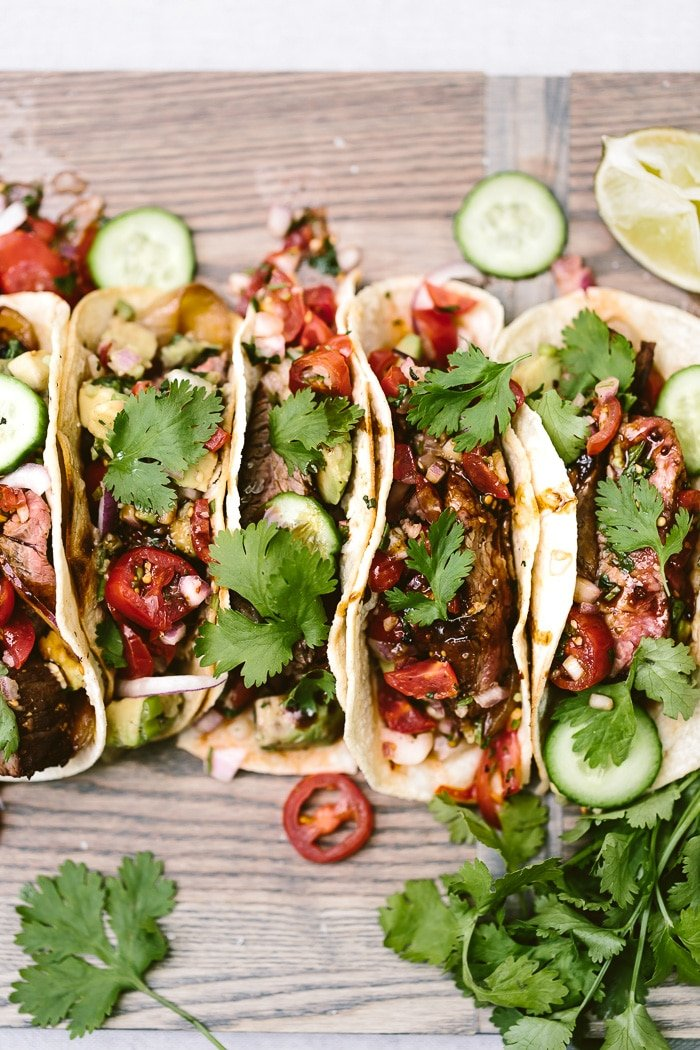 Recipe for Grilled Flank Steak Tacos with a foolproof flank steak marinade placed on a cutting boards