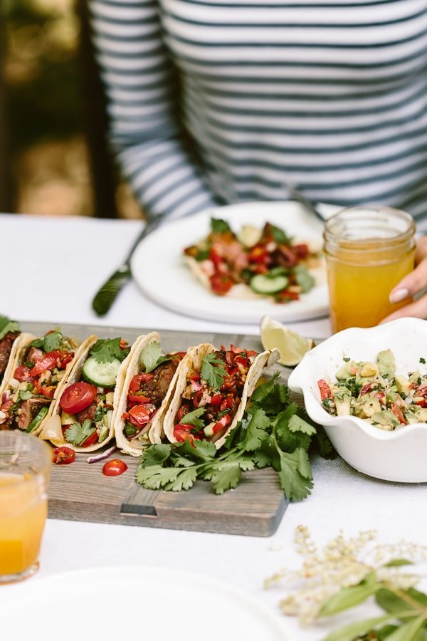 Flank Steak Taco Recipe served on a cutting board in front of a woman at at table