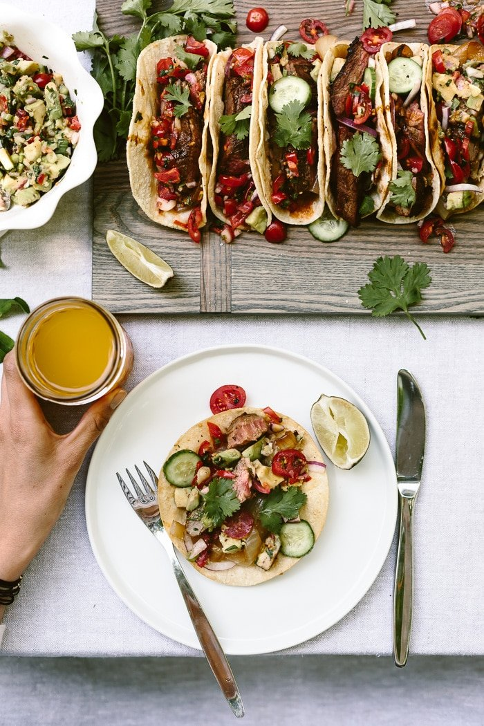 flank steak tacos placed on a cutting board.