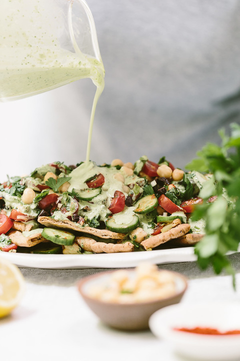 Vegan Greek Nachos Recipe: Toasted Pita Bread Topped off with tomatoes, cucumber, scallions, and parsley and drizzled with green tahini sauce.